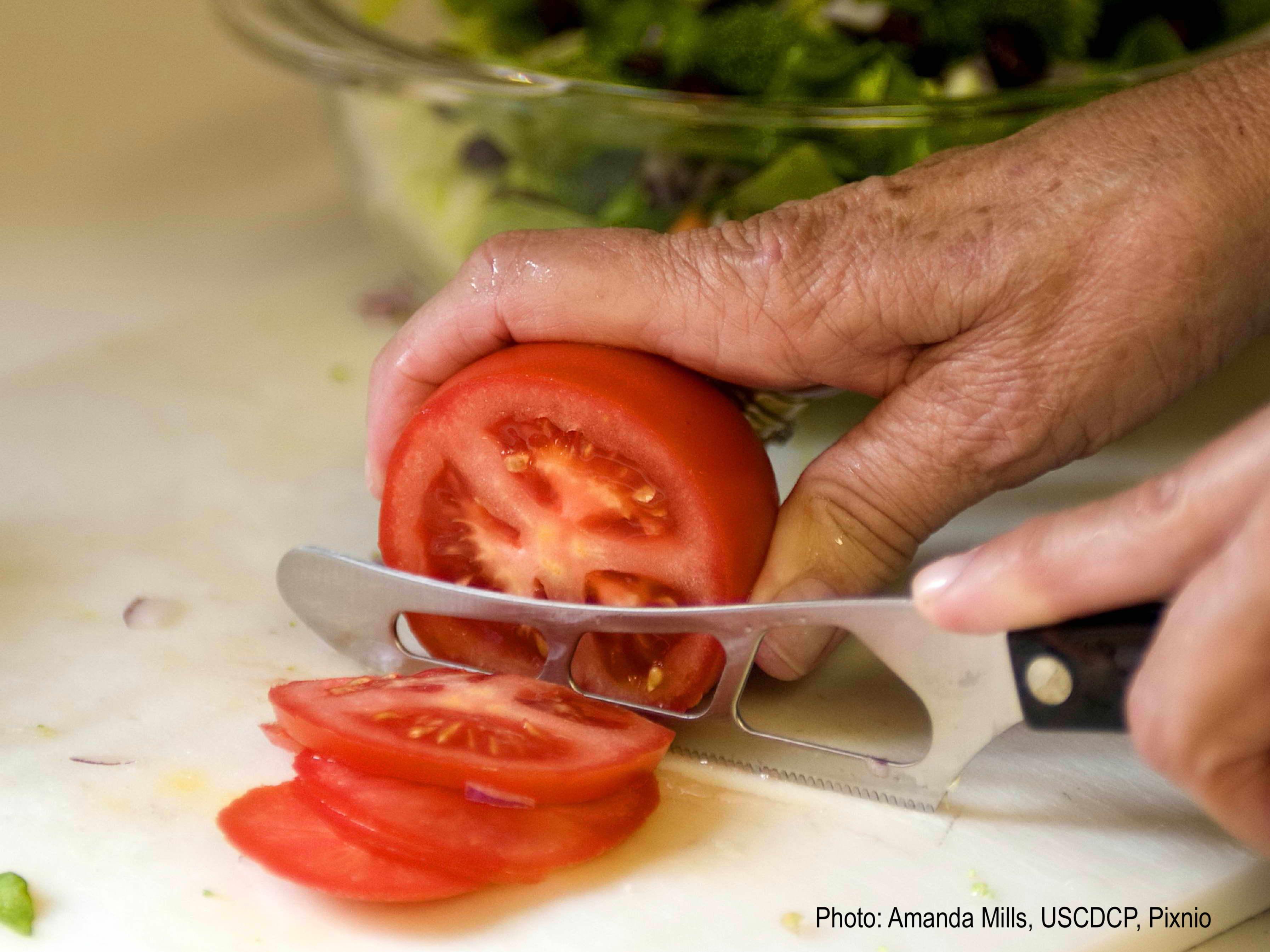 Main qui tranche une tomate.